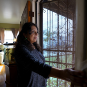 Esther Lopez settles in at home in Chula Vista after work at a nearby grocery store.(Nelvin C. Cepeda / The San Diego Union-Tribune)